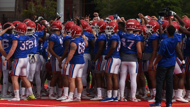 The LA Tech Bulldogs huddle up at the start of their practice during the teams annual Football Fan Fest.