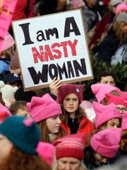 A woman holds a sign amidst a sea of pink caps before