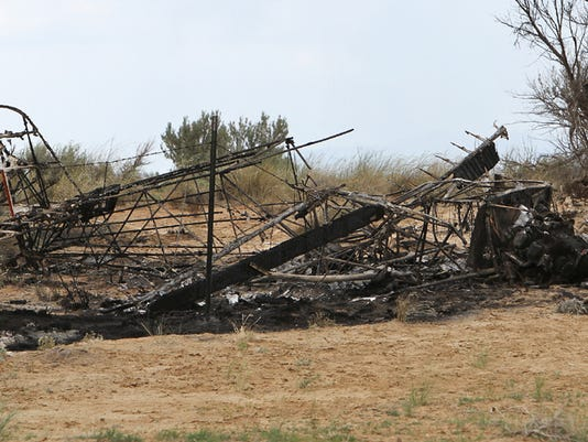 The charred skeleton of a single-engine plane is seen at the scene of a fatal plane crash at the Aztec Airport on Saturday, May 18, 2013. The pilot of the plane Michael Arnold, 62, lost control of the aircraft during takeoff and died on impact, according to New Mexico State Police. Arnold was the airport manager and former mayor of Aztec.