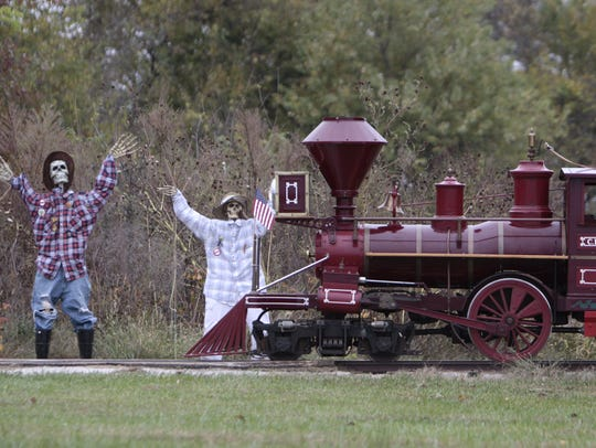 A train steams past tow of near 130 life-size figures