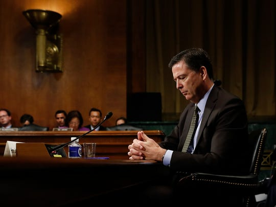 James Comey pauses as he testifies on Capitol Hill