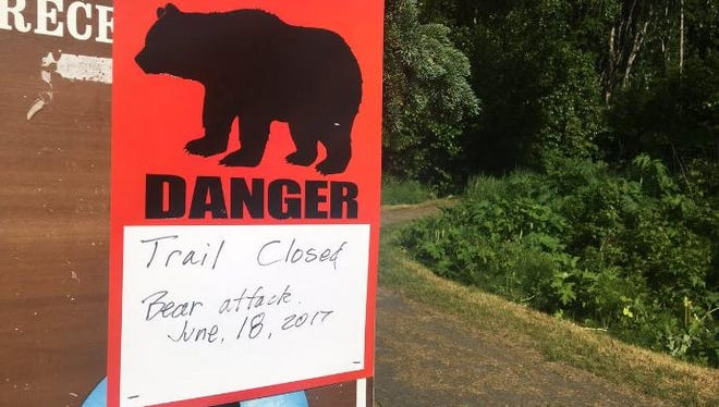 A sign indicates the trail is closed where Sunday a black bear fatally mauled a 16-year-old boy during a running race.
