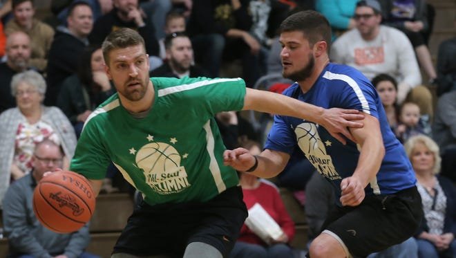North alum Brook Turson, who scored over 2,000 points in his Plymouth career, tries to drive past Lex grad Mason Willeke of the South in the 40th News Journal All-Star Classic alumni game.