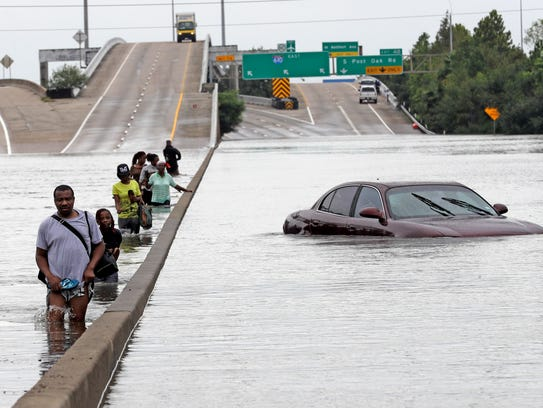 Evacuees wade down a flooded section of Interstate