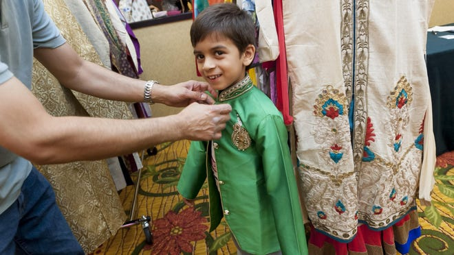 Five-year-old Hamza Hasham of Troy tries on a sherwani suit while shopping at the Eid Chand Raat Mela market festival in the Troy Marriott on Tuesday. The Kahkeshan Art Council event coincides with Eid al-Fitr, the Muslim holiday that ends the holy month of Ramadan.