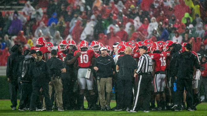 Georgia Bulldogs in a huddle in the first half of a NCAA football game between Georgia and Kentucky in Athens, Ga., on Saturday, Oct. 19, 2019.