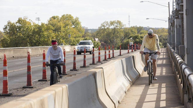 Mike Stanley, right, bikes across Longhorn Dam on South Pleasant Valley Road in East Austin on Nov. 20. With the passage of Proposition B, Austin will get a third pedestrian bridge near the Longhorn Dam.