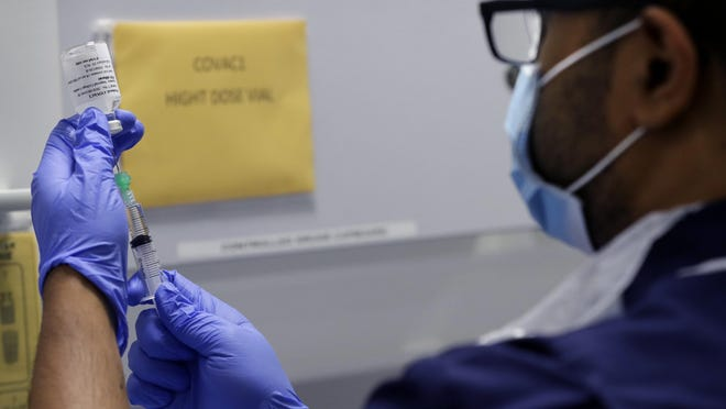 Senior Clinical Research Nurse Ajithkumar Sukumaran prepares the vaccine, at a clinic in London, Wednesday, Aug. 5, 2020. Imperial College is working on the development of a COVID-19 vaccine.