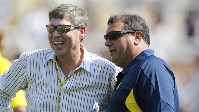Michigan AD Dave Brandon, left. talks with head coach Brady Hoke as the team warms up on the field before the start  of their season opener against Western Michigan in Ann Arbor, on Saturday, September  3,  2011.