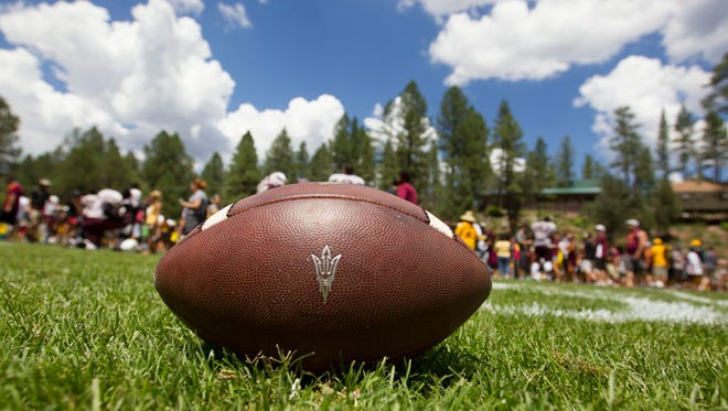 A football sits in the grass at ASU's Camp Tontozona near Payson on Saturday, Aug. 18, 2014.