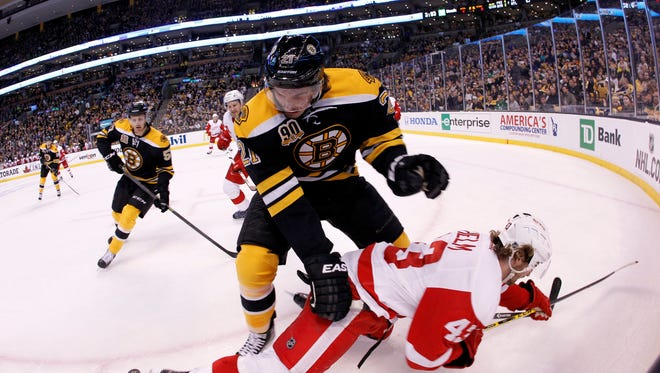 Boston Bruins right wing Loui Eriksson (21) sends Detroit Red Wings center Darren Helm (43) into the boards during the first period in game two of the first round of the 2014 Stanley Cup Playoffs.