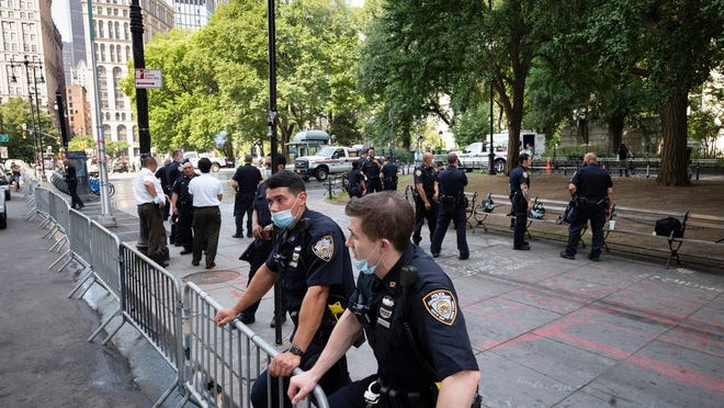 Police stand behind barricades at a park adjacent to City Hall, Wednesday, July 22, 2020, in New York. Police in riot gear cleared a month-long encampment of protesters and homeless people from the park earlier in the morning.