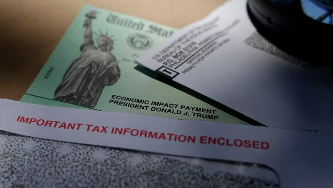 FILE - In this April 23, 2020, file photo, President Donald Trump's name is seen on a stimulus check issued by the IRS to help combat the adverse economic effects of the COVID-19 outbreak. AP Photo/Eric Gay, File