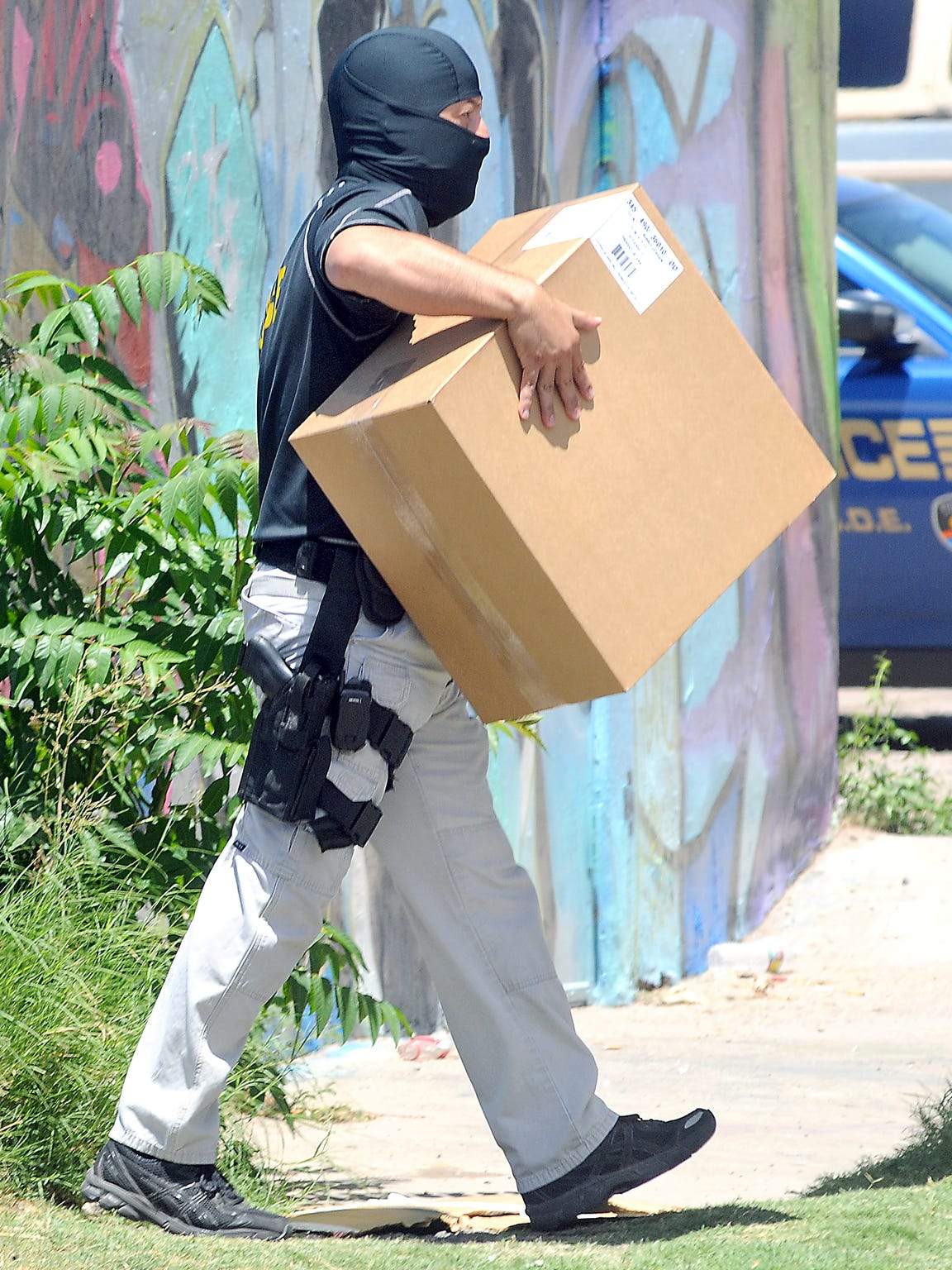 A masked DEA agent carries evidence out of Phat Glass, 1211 E. Idaho Ave., on July 25, 2012, while federal and local law enforcement officers raided 14 area smoke shops as part of a wider investigation into synthetic drug sales.