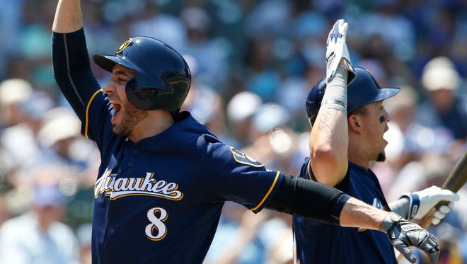 Ryan Braun (left) of the Milwaukee Brewers celebrates with teammate Hernan Perez after hitting a home run Thursday afternoon in the third inning against the Chicago Cubs at Wrigley Field.