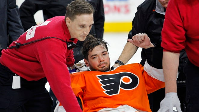 Philadelphia Flyers goalie Michal Neuvirth gives a thumbs-up as he is taken off the ice on a stretcher after collapsing early in the first period of Saturday's game.