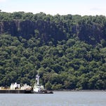 A rescue boat searches the area near the barge that was struck by a boat in the middle of the Hudson, as seen from Irvington on July 27, 2013.