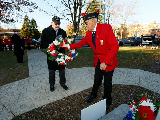 Color Guard escort John Pendergast hands a wreath to Committee Chairman Anthony Romano during the Memorial and Veterans Day Association of Morristown and Morris Township's annual Veterans Day services starting with laying of wreaths and Honor Guard salute at J. Robert Tracey Veterans Memorial Park. November 10, 2017. Morristown, New Jersey