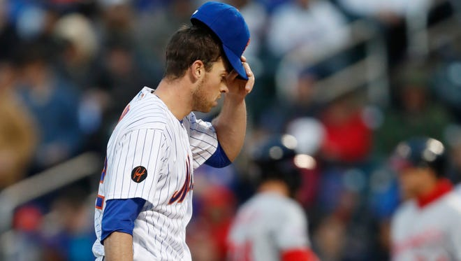 New York Mets starting pitcher Steven Matz pauses during the first inning of the team's baseball game against the Washington Nationals, Wednesday, April 18, 2018, in New York.