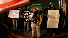 Protesters hold signs Nov. 22, 2014, along a stretch