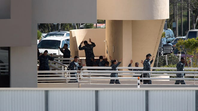 Naval Medical Center Sand Diego personnel with their hands in the air, help law enforcement clear a building on the campus of the facility following a report of gunshots at a building of the hospital and ambulatory complex, Tuesday, Jan. 26, 2016, in San Diego.