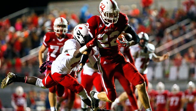 Reeds Spring High School wide receiver Adam Taylor (22) runs through the arms of Bulldogs defensive back Damarcus Mason (4) during second quarter action of the Wolves' game against Central High School at Carl Langley Field in Reeds Spring, Mo. on Oct. 9, 2015. Reeds Spring won the game 35-24.