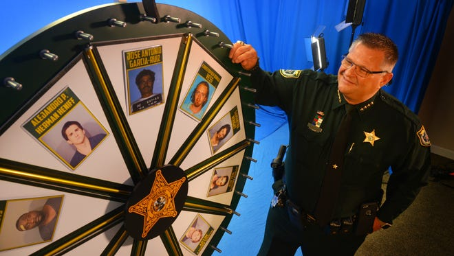 """Brevard County Sheriff Wayne Ivey stands in the Brevard County Sheriff's Office media production center in Titusville next to the """"Wheel of Fugitive."""""""