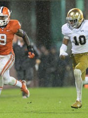 Clemson running back Wayne Gallman (9) runs away from Notre Dame safety Max Redfield last Saturday.