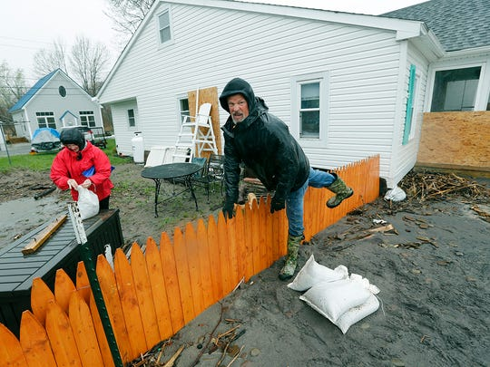 Bob Jones, a former teacher who also has coached high school sports, rushes over the fence to sandbag his lakefront house on Sandy Harbor Drive in Hamlin as his wife Judy ties others.