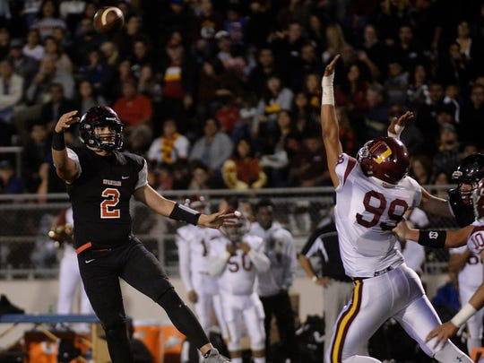 Rio Mesa quarterback Austin Maciel throws a pass over Oxnard's Joseph Gutierrez during the Spartans' win over their rival earlier this season. Maciel was named the county's Offensive MVP by the coaches' association.