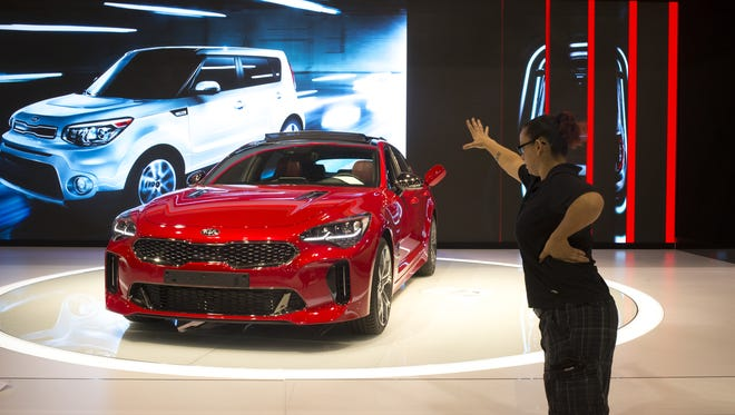 Cassandra Anderson directs lighting on a Kia Stinger, November 22, 2017, on move-in day at the 2018-model Arizona International Auto Show at Phoenix Convention Center, 100 North Third Street, Phoenix.