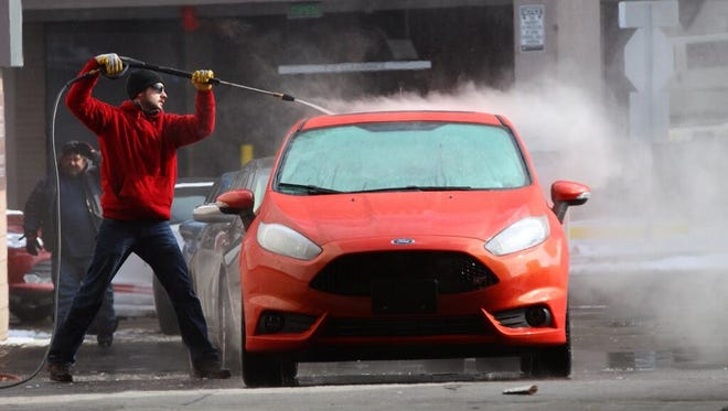 Agisilaos Stathopoulos braves the cold temps to wash cars going into the auto show.