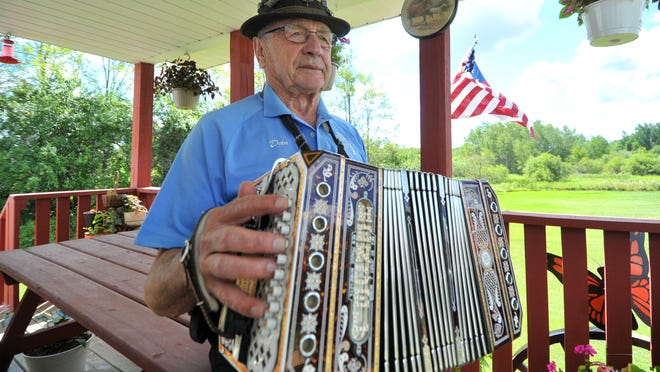 Dan Gruetzmacher, town of Texas, plays his concertina recently at his home.