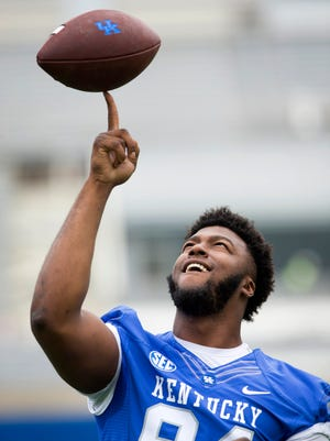Kentucky defensive tackle Courtney Miggins spins a football on his finger while killing time between portraits during the team's annual NCAA college football media day at Commonwealth Stadium in Lexington, Ky., Friday, Aug. 7, 2015.