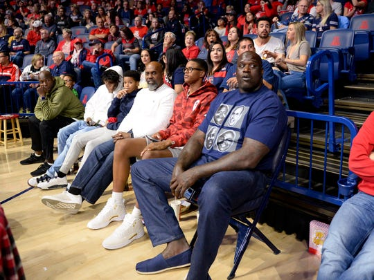 Former NBA player and current television analyst Shaquille O'Neal watches the Arizona Wildcats play the Sacred Heart Pioneers next to his son Shareef O'Neal during the second half at McKale Center in November.