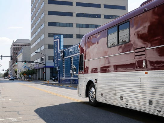 A bus pulls up to the old Greyhound bus station for
