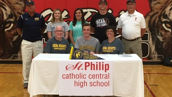 St. Philip senior Jack Greenman is surrounded by his parents, Todd and Caroline Greenman, as he signed a letter of intent to run at Siena Heights University.  Standing in back (L-R) is Siena Heights cross country and track head coach Tim Bauer, sisters Carrie Greenman and Jenna Gangi, St. Philip cross country coach Ray Yager and track coach Jeff Minier. Missing from photo is sister Anna Greenman.