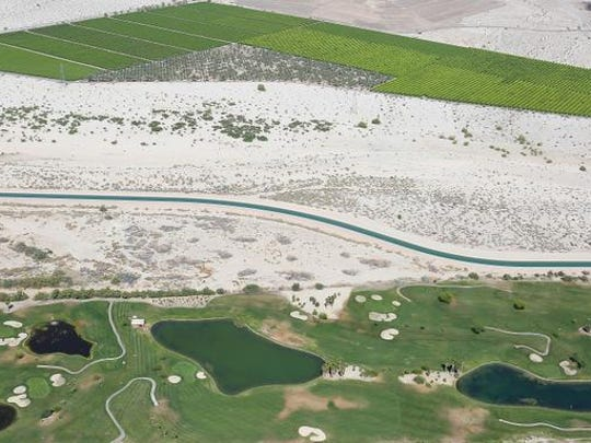 The Coachella Canal runs through open desert between agricultural fields and a golf course in Indio.