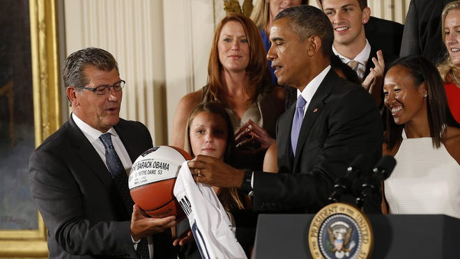 President Barack Obama receives a game ball last year from Connecticut coach Geno Auriemma during a ceremony honor the 2015 national champions.