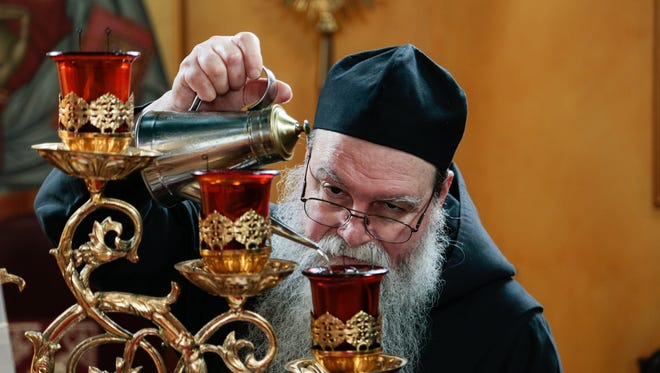 Father Basil pours oil into lamps on the altar inside the monastery church.