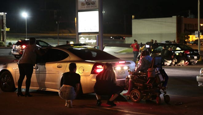 Protesters hide behind cars after shots were fired Tuesday, Aug. 9, 2016, in Ferguson, Mo., during a demonstration on the second anniversary of Michael Brown's death. Witnesses told an Associated Press reporter that a car sped through a group of protesters who were blocking a street during the demonstration marking two years since the unarmed black 18-year-old's fatal shooting by a white police officer. They said the car struck a young man so hard that he flew into the air. As the car drove away, shots were fired, they said.