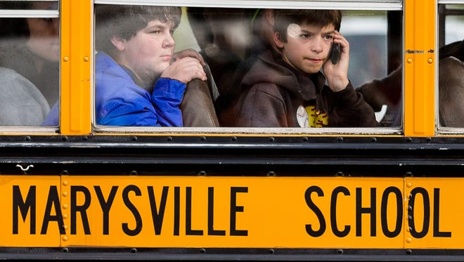 A boy attempts to make a call from his school-bus seat Oct. 24, 2014, while heading to a reunification center following a shooting at Marysville Pilchuck High School in Marysville, Wash.