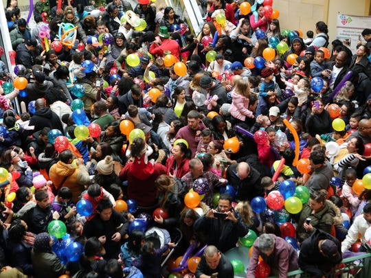 "People reach out for the balloons during the ""Ring in the New Year at Noon"" at New Roc City in New Rochelle, Dec. 31, 2016. The 7th annual event, benefiting the Westchester Children's Museum, included giveaways, activities and a meet and greet with New York Ranger alum, Ron Greschner."