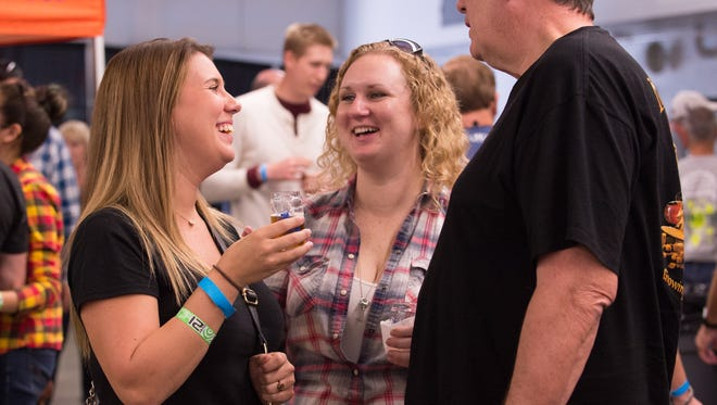 Amy Seighman (left) of Charleston, S.C., Laura Horzelski of Baton Rouge, La., and Charlie Seighman of Charleston, S.C., at the Delaware Wine and Beer Festival at the Delaware State Fairgrounds in Harrington.