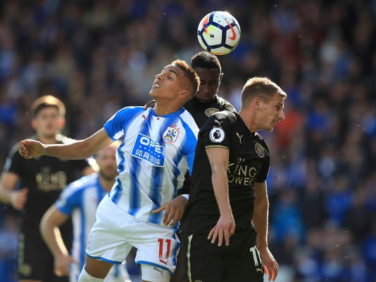 Huddersfield Town's Abdelhamid Sabiri, left, battles with Leicester City's Marc Albrighton, right and Wilfred Ndidi during the Premier League soccer match between Huddersfield and Leicester City,  at the John Smith's Stadium, in Huddersfield, England, Saturday, Sept. 16, 2017. (Mike Egerton/PA via AP)