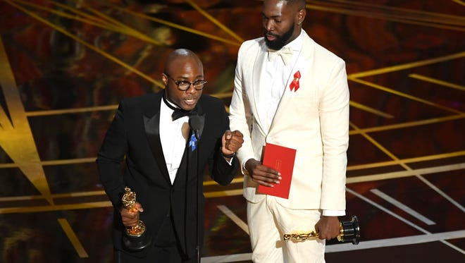 Writer/director Barry Jenkins (L) and writer Tarell Alvin McCraney accept Best Adapted Screenplay for 'Moonlight' onstage during the 89th Annual Academy Awards.