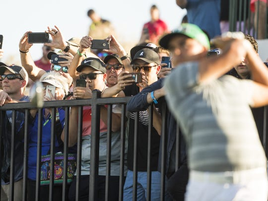Fans watch as Rickie Fowler tees off on the 18th hole