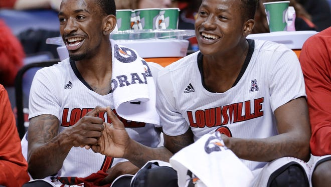 Louisville's Russ Smith, left, and Terry Rozier laugh on the bench during the final minutes of Louisville's 94-65 win over Houston in an NCAA college basketball game in the semifinals of the American Athletic Conference men's tournament Friday, March 14, 2014, in Memphis, Tenn. Smith led Louisville with 42 points.