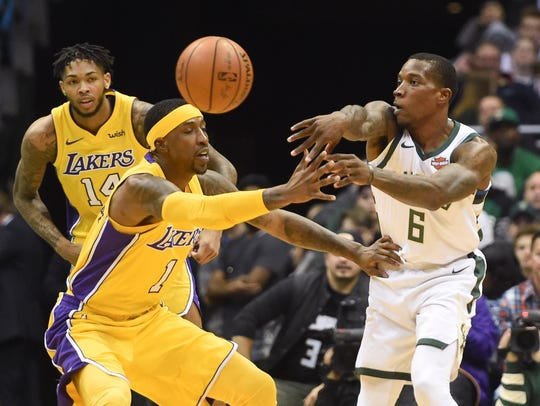 Newly acquired Bucks guard Eric Bledsoe passes against Lakers guard Kentavious Caldwell-Pope on Saturday.