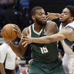 The Minnesota Timberwolves' Karl-Anthony Towns, right, tries to get to the ball held by the Milwaukee Bucks' Greg Monroe in the first half Friday in Minneapolis.